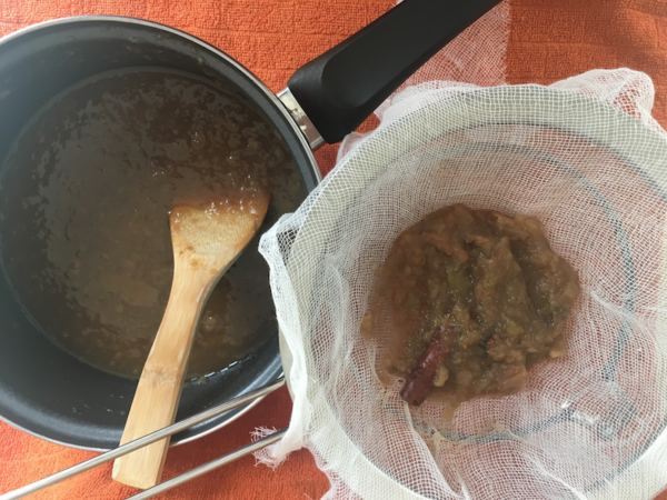 To strain the apple cider, place cheesecloth over the mesh strainer and slowly pour in the cider.